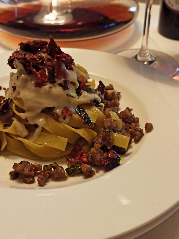 Tagliatelle con salsiccia, zucchine, crema di parmigiano e peperoni cruschi